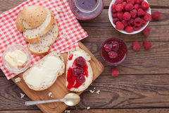Raspberries berries, raspberries jam, butter and bread on wooden table. Royalty Free Stock Photography