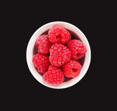 Raspberries in a black ceramic bowl. Ripe and tasty raspberries isolated on black background. Top view Royalty Free Stock Image