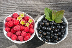 Raspberries and black currants in two cups. On wooden surface the view from the top Royalty Free Stock Photos