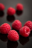 Raspberries on a black stone. Lot of raspberries on a black stone with reflections Royalty Free Stock Photography