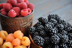 Raspberries are black, yellow and red in clay ware on a wooden table.n stock photography
