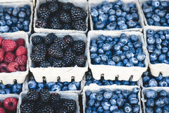 Raspberries, blackberries and blueberries market display. Raspberries, blackberries and blueberries background in small baskets for sale at market Stock Images