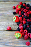 Raspberries and blackberries on the boards Royalty Free Stock Images