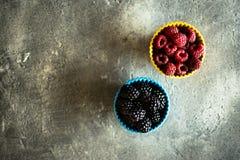 Raspberries and Blackberries in Ceramic Bowls on Rustic Backgrou. Nd Stock Photos