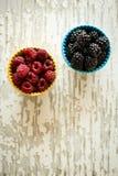 Raspberries and Blackberries in Ceramic Bowls on Rustic Backgrou. Nd Royalty Free Stock Image