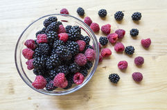 Raspberries and blackberries in a glass jar on a wooden table. Royalty Free Stock Photo