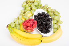 Raspberries Blackberries Grapes and Bananas on White Royalty Free Stock Image