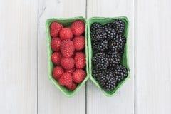 Raspberries and blackberries in a separate cardboard box. Stock Photo