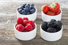 Raspberries, blackberries, strawberries and blueberries in bowls. Close-up Stock Images