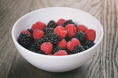 Raspberries and blackberries in white bowl on wood. Table, vintage toned Royalty Free Stock Photos