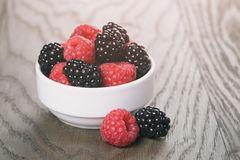 Raspberries and blackberries in white bowl on wood. Table, vintage toned Stock Photo