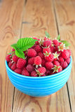 Raspberries in the blue bowl. Raspberries in the blue ceramic bowl on the wooden table Stock Photos