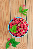 Raspberries in the blue bowl. Raspberries in the blue ceramic bowl on the wooden table Royalty Free Stock Image