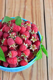 Raspberries in the blue bowl. Raspberries in the blue ceramic bowl on the wooden table Royalty Free Stock Photography