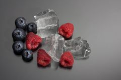 Raspberries and blueberries on black background. Raspberries and blueberries arranged on black background with ice cubes Stock Images