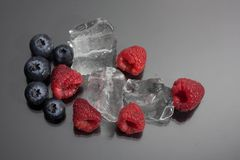 Raspberries and blueberries on black background. Raspberries and blueberries arranged on black background with ice cubes Stock Photos