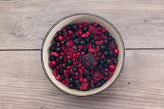 Raspberries, blueberries, blackberries in a round bowl. On a wooden table Stock Photos