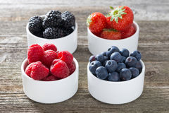 Raspberries, blueberries, blackberries and strawberries in bowls. Close-up Stock Image