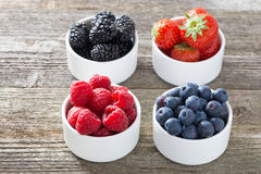 Raspberries, blueberries, blackberries and strawberries in bowls. Top view, horizontal Royalty Free Stock Photos