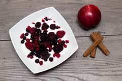 Raspberries, blueberries, blackberries in a white plate with natural yogurt, and an apple and cinnamon sticks on a table. Raspberries, blueberries, blackberries Royalty Free Stock Images