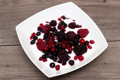 Raspberries, blueberries, blackberries in a white plate on a table Stock Photography