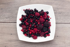 Raspberries, blueberries, blackberries in a white plate. On a wooden table Stock Photo