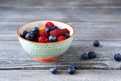 Raspberries and blueberries in a bowl on boards Royalty Free Stock Photography