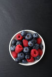 Raspberries and blueberries in a bowl. Food on slate Stock Photo