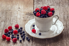 Raspberries and blueberries in ceramic bowl. Seasonal concept Royalty Free Stock Photos