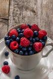 Raspberries and blueberries in ceramic bowl Stock Photo