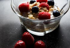 Healthy breakfast. Bowl with raspberries and blueberries. Raspberries, blueberries, cereals and yogurt in a glass bowl on a black surface. Healthy breakfast for Royalty Free Stock Image