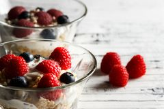 Healthy breakfast. Bowl with raspberries and blueberries. Raspberries, blueberries, cereals and yogurt in a glass bowl on wooden slats. Healthy breakfast for a Royalty Free Stock Photo