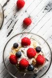 Healthy breakfast. Bowl with raspberries and blueberries. Raspberries, blueberries, cereals and yogurt in a glass bowl on wooden slats. Healthy breakfast for a Royalty Free Stock Image