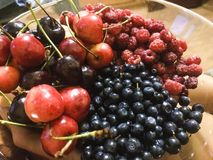 Raspberries, blueberries, cherries on a plate. Of delicious fruits Royalty Free Stock Photo
