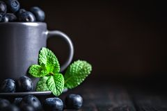 Raspberries and blueberries in a Cup on a dark background. Summer and healthy food concept. Background with copy space royalty free stock photography