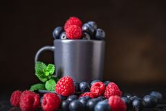 Raspberries and blueberries in a Cup on a dark background. Summer and healthy food concept. Background with copy space royalty free stock photos