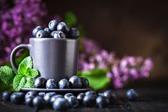 Raspberries and blueberries in a Cup on a dark background. Summer and healthy food concept. Background with copy space stock image