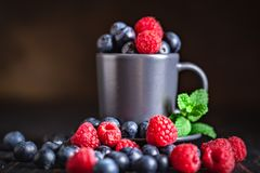 Raspberries and blueberries in a Cup on a dark background. Summer and healthy food concept. Background with copy space royalty free stock images