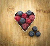 Raspberries and blueberries. Fresh organic raspberries and blueberries in heart shape Stock Photos