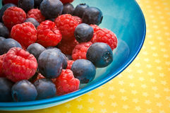 Raspberries and blueberries. Fruit raspberries and blueberries in a blue bowl Royalty Free Stock Image