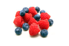 Raspberries and blueberries isolated on white. A bunch of plump delicious raspberries and blueberries isolated on white Royalty Free Stock Photos