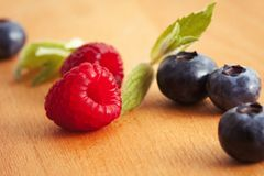 Raspberries and blueberries with mint leaves on a wooden surface Stock Photos