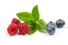 Raspberries and blueberries with mint on white background Royalty Free Stock Image