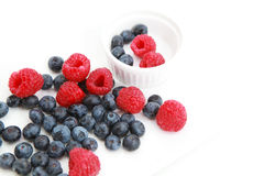 Raspberries and blueberries over white Royalty Free Stock Photos