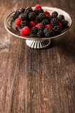 Raspberries and blueberries on a plate in the Oriental style. Wooden background Royalty Free Stock Photos