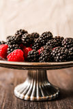 Raspberries and blueberries on a plate in the Oriental style Stock Photos