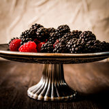 Raspberries and blueberries on a plate in the Oriental style. Wooden background Stock Image