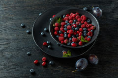 Raspberries, blueberries, plum and dogwood. fresh berries on plate. Ceramic bowl with assortment berries on black wood background Royalty Free Stock Image