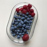 Raspberries, blueberries & a single strawberry atop a glass dish - VEGAN - VEGETARIAN. A berry is a small, pulpy, and often edible fruit. Berries are typically Stock Photos