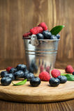 Raspberries and blueberries in a small  bucket Stock Photos